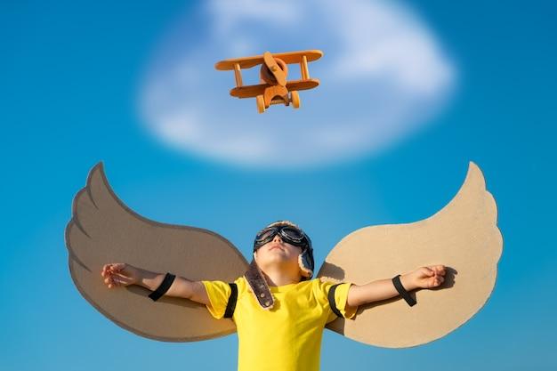 Glückliches kind, das mit spielzeugflügeln gegen hintergrund des blauen himmels spielt. kind, das spaß im freien im sommer hat.