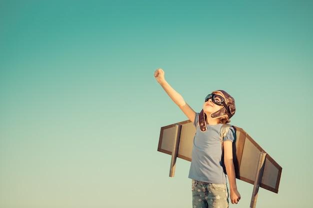 Glückliches kind, das mit spielzeugflügeln gegen sommerhimmelhintergrund spielt. retro getönt