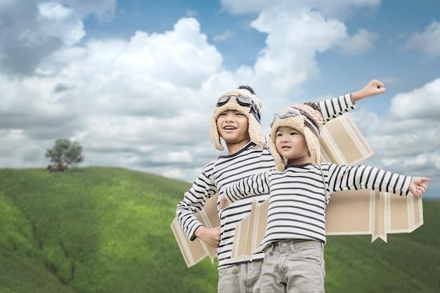 Glückliches kind, das mit spielzeugflügeln gegen sommerhimmelhintergrund spielt.