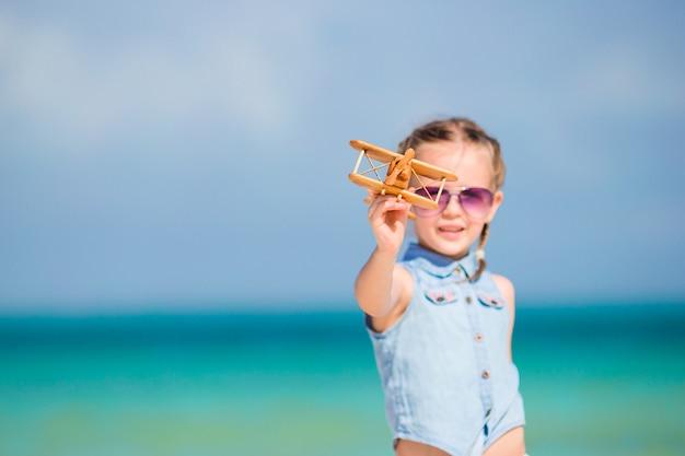 Glückliches kind, das mit spielzeugflugzeug auf dem strand spielt.