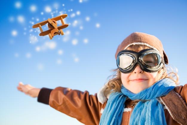 Glückliches kind, das mit spielzeugflugzeug gegen blauen winterhimmelhintergrund spielt