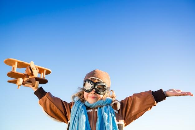 Glückliches kind, das mit spielzeugflugzeug gegen hintergrund des blauen himmels spielt. kopieren sie platz für ihren text
