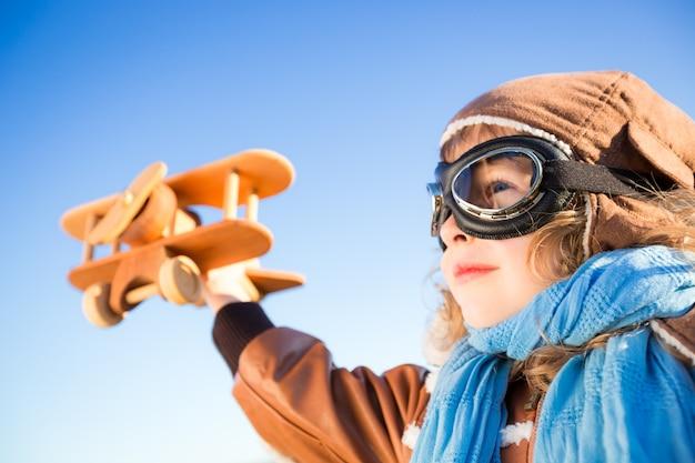 Glückliches kind, das mit spielzeugflugzeug gegen hintergrund des blauen himmels spielt