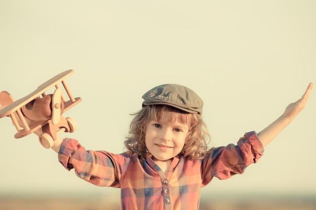 Glückliches kind, das mit spielzeugflugzeug gegen sommerhimmelhintergrund spielt