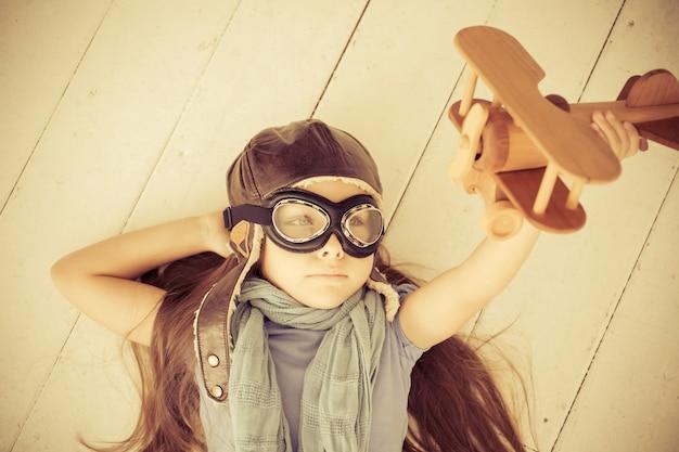 Glückliches kind, das mit spielzeugflugzeug spielt. kind, das zu hause auf holzboden liegt. retro-getönt