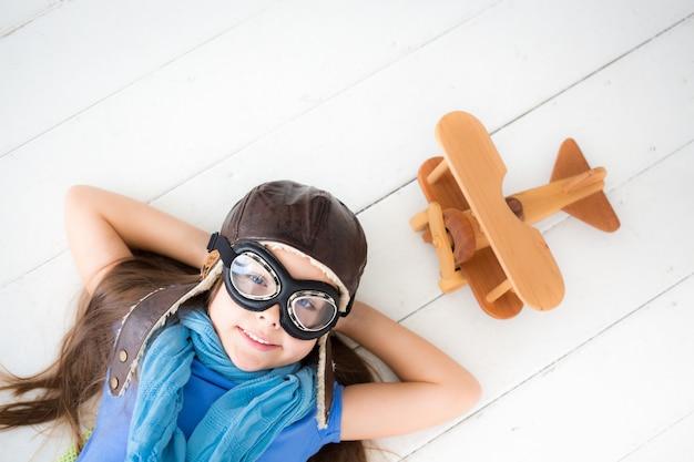 Glückliches kind, das mit spielzeugflugzeug spielt. kind, das zu hause auf holzboden liegt