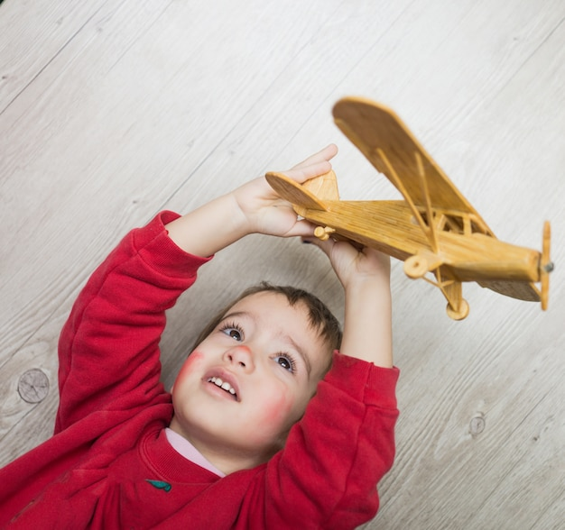 Glückliches kind, das mit spielzeugflugzeug spielt