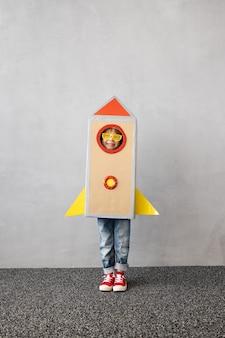 Glückliches kind, das mit spielzeugpapierrakete gegen graue betonwandoberfläche spielt