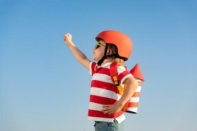 Glückliches kind, das mit spielzeugrakete gegen blauen himmelhintergrund spielt. kind, das spaß im freien im sommer hat.
