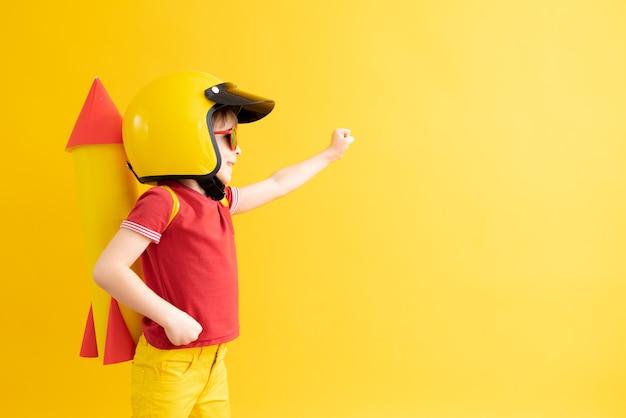 Glückliches kind, das mit spielzeugrakete gegen gelbe oberfläche spielt
