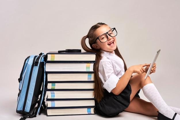 Glückliches kind, das mit tablett studiert