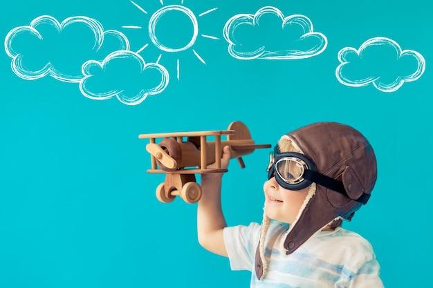 Glückliches kind, das mit weinleseholzflugzeug gegen blaue wand spielt.