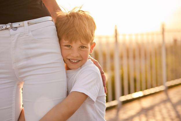 Glückliches kind, das mutter auf der straße umarmt
