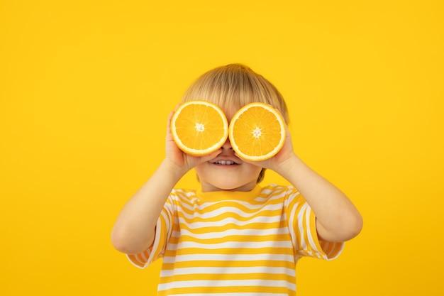 Glückliches kind, das orange hält