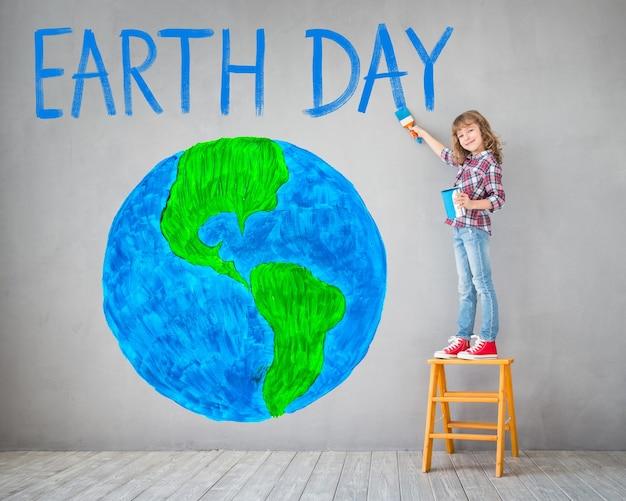 Glückliches kind, das planeten an der wand malt. kind hat spaß zu hause. frühlingsferien konzept zum tag der erde