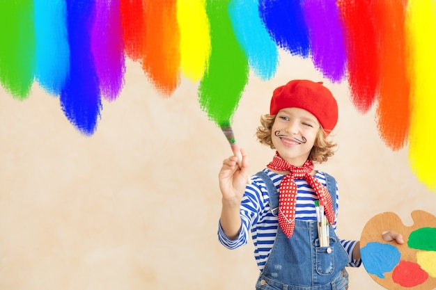 Glückliches kind, das regenbogen zu hause malt.