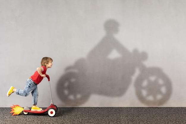 Glückliches kind, das roller reitet