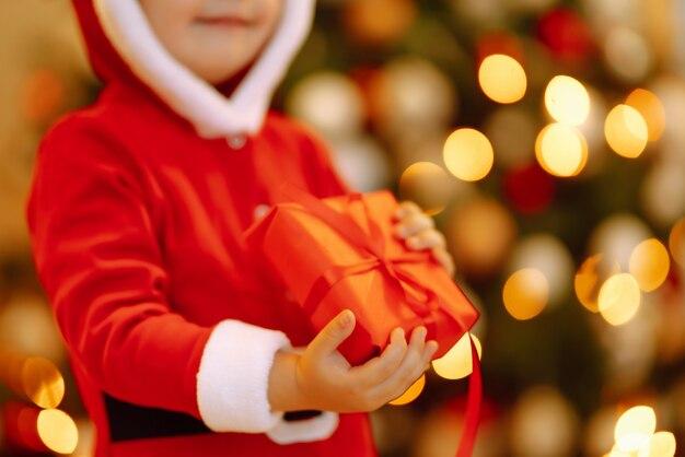 Glückliches kind, das rote geschenkbox auf den hintergrundlichtern hält.