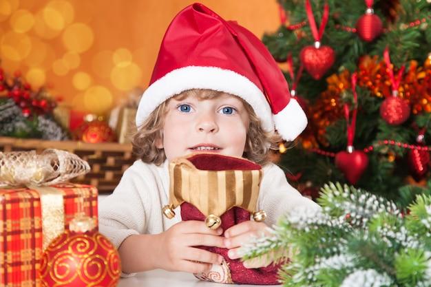 Glückliches kind, das rote socke gegen weihnachtsbaum mit dekorationen hält