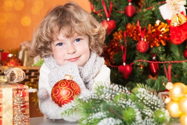 Glückliches kind, das roten ball gegen weihnachtsbaum mit dekorationen hält