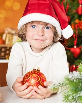 Glückliches kind, das roten ball gegen weihnachtsdekorationen hält