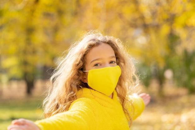 Glückliches kind, das schutzmaske im freien in einem park im herbst trägt.