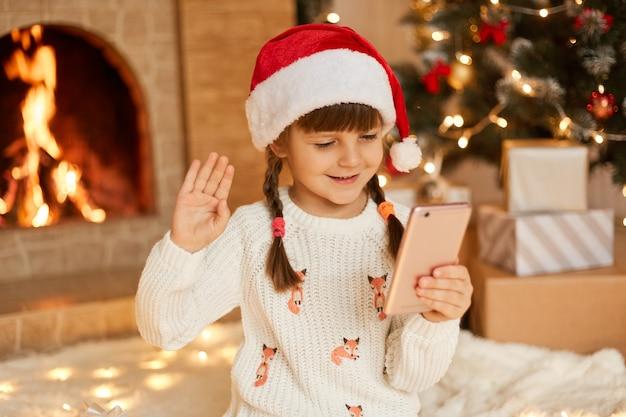 Glückliches kind, das smartphonebildschirm und winkende hand betrachtet, freunde oder verwandte per video anruft, bleibt zu weihnachten in den weihnachtsferien zu hause und trägt einen weißen pullover und einen festlichen weihnachtsmannhut in der nähe des kamins.