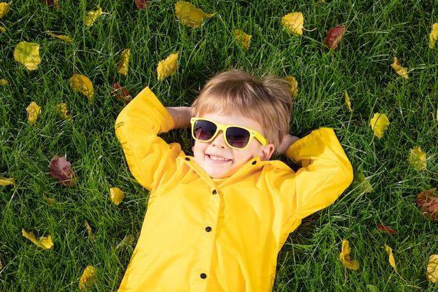 Glückliches kind, das spaß im freien im herbstpark hat