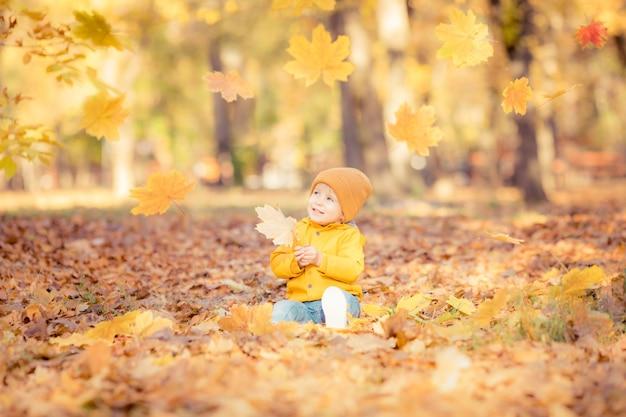 Glückliches kind, das spaß im herbstpark hat. lustiges kind, das draußen spielt.