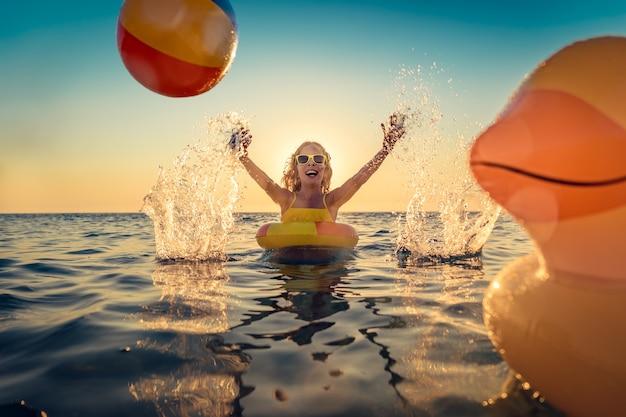 Glückliches kind, das spaß in den sommerferien hat. kind spielt mit gummiente und ball im meer. gesundes lebensstilkonzept. spring break, frühjahrsurlaub, frühjahrsferien!