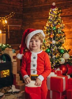 Glückliches kind, das spaß mit geschenk hat, glücklicher kleiner lächelnder junge mit weihnachtsgeschenksocken