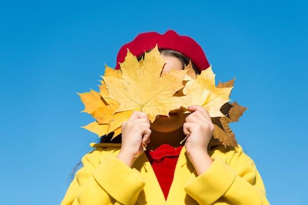 Glückliches kind, das spaß mit herbstahornblättern hat, lustige stimmung