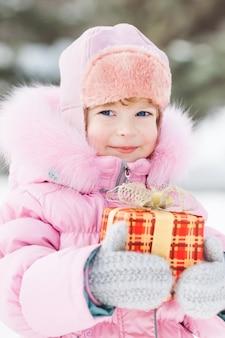 Glückliches kind, das weihnachtsgeschenk im winterpark hält außenaufnahme