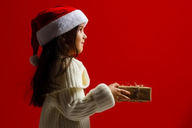 Glückliches kind, das weihnachtsgeschenke auf einem roten hintergrund hält