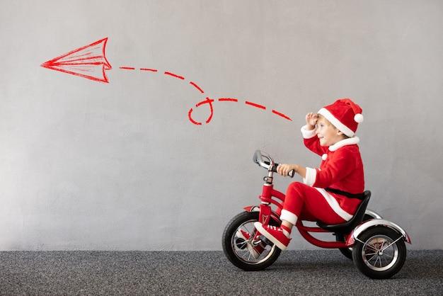 Glückliches kind, das weihnachtskostüm trägt kind, das fahrrad weihnachtsferienkonzept reitet
