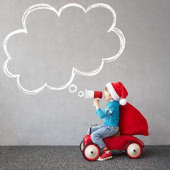 Glückliches kind, das weihnachtskostüm trägt lustiges kind, das durch lautsprecher schreit