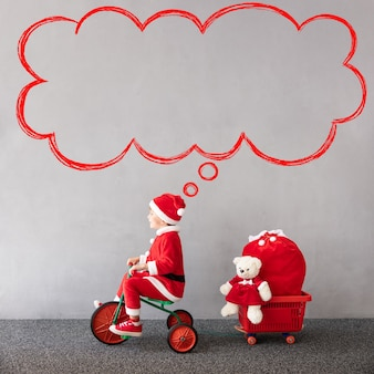 Glückliches kind, das weihnachtskostüm weihnachtsfeiertagskonzept trägt