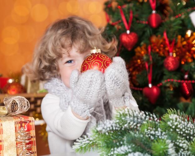 Glückliches kind, das weihnachtskugel gegen verzierten tannenbaum hält