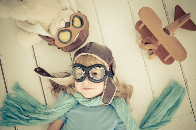 Glückliches kind, das zu hause mit spielzeugflugzeug aus holz spielt. retro-getönt