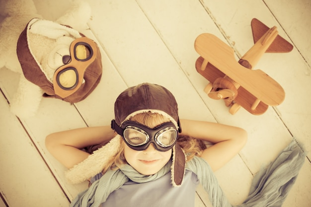 Glückliches kind, das zu hause mit spielzeugflugzeug spielt. retro-getönt