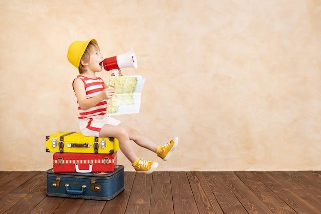 Glückliches kind, das zu hause spielt. lächelndes kind, das von sommerferien und reisen träumt. vorstellungskraft und freiheitskonzept