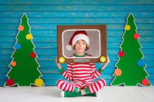 Glückliches kind, das zu hause spielt. lustiges kind an heiligabend