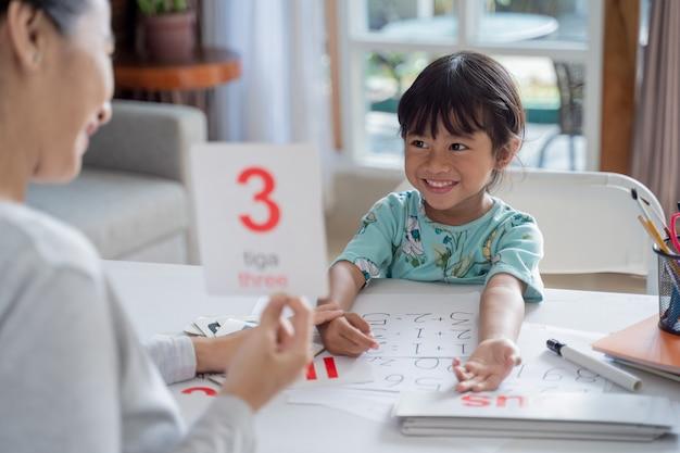 Glückliches kind, das zusammen mit eltern zu hause lernt und lernt