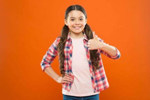 Glückliches kind daumen hoch. kindertag. kindheitsglück. kleines mädchen orange hintergrund. kindermode. lächelndes schulmädchen. arbeiteruniform. kind langes haar. kariertes hemd für kleine mädchen. den erfolg spüren.