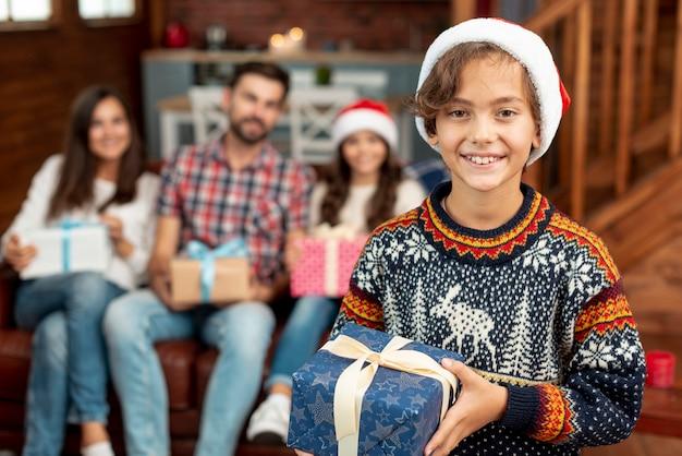 Glückliches kind des mittleren schusses mit weihnachtsgeschenk