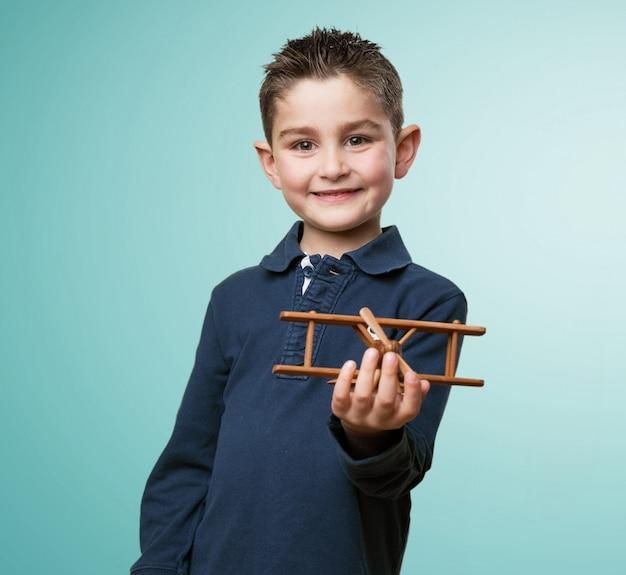 Glückliches kind ein spielzeug flugzeug hält