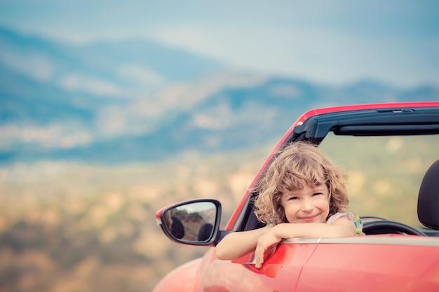 Glückliches kind fährt mit dem auto in den bergen kind, das spaß im roten cabriolet sommerferienkonzept hat