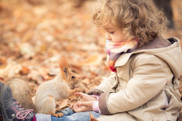 Glückliches kind füttert ein kleines eichhörnchen im herbstpark