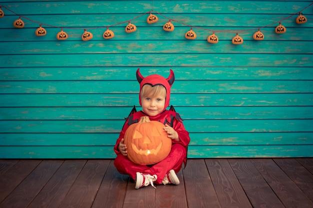 Glückliches kind gekleidetes halloween-kostüm, das kürbis hält