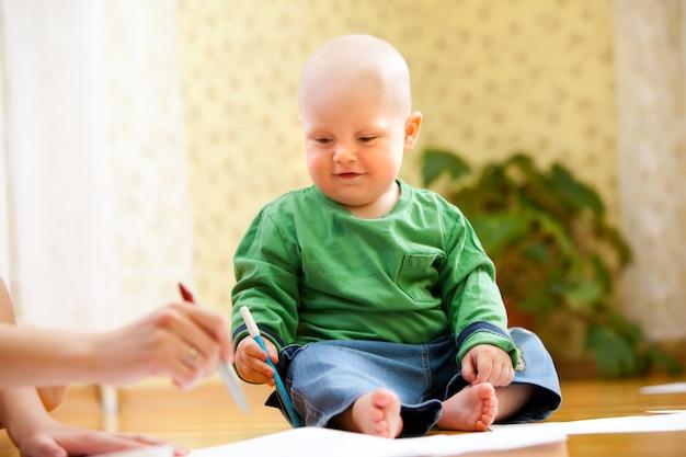 Glückliches kind hält filzstifte in der hand und zeichnet. foto des babys mit dem verschwommenen hintergrund